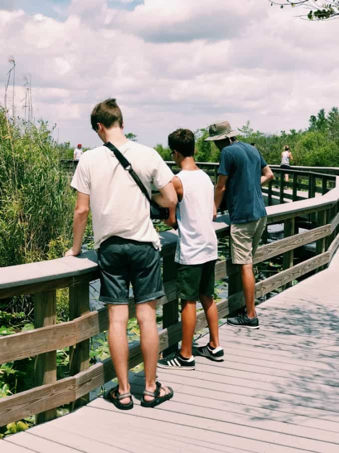 Three gentlemen enjoy watching for alligators and other wildlife from one of the many boardwalk areas found at Everglades National Park in Florida.