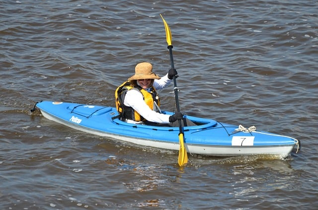 Woman paddles through the ocean in a single person kayak.